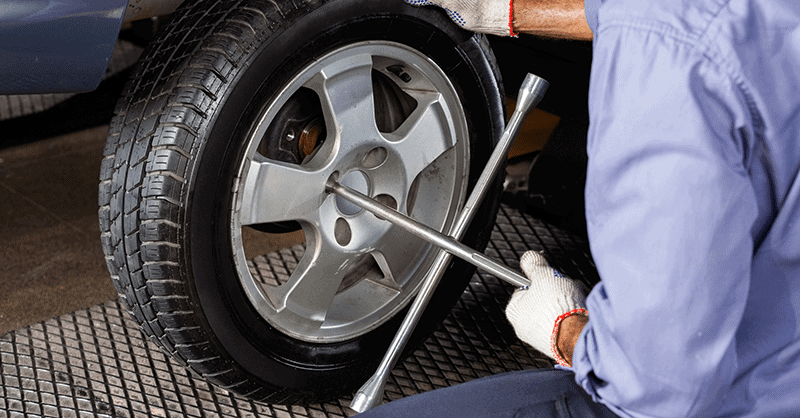 man using lug nut wrench